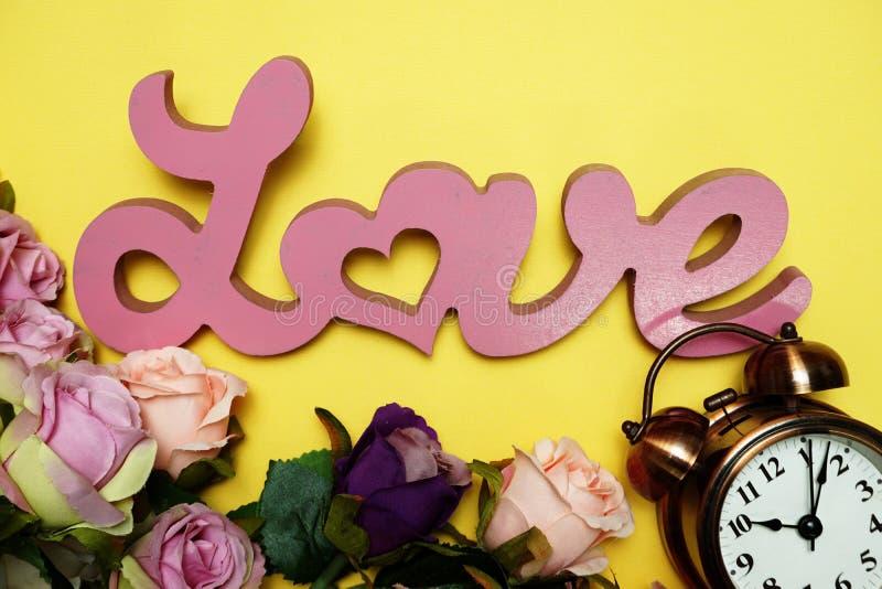 Αλφάβητο λέξης αγάπης και εκλεκτής ποιότητας ξυπνητήρι με την ανθοδέσμη τριαντάφυλλων με το διαστημικό αντίγραφο στο κίτρινο υπόβ στοκ εικόνες