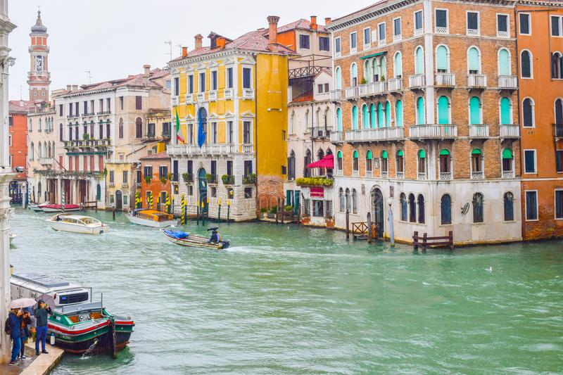 Αμάξια ταξί νερού taxis/και άλλες βάρκες που πλέουν μεταξύ των ζωηρόχρωμων γοτθικών ενετικών κτηρίων τη βροχερή ημέρα στο μεγάλο  στοκ φωτογραφίες με δικαίωμα ελεύθερης χρήσης