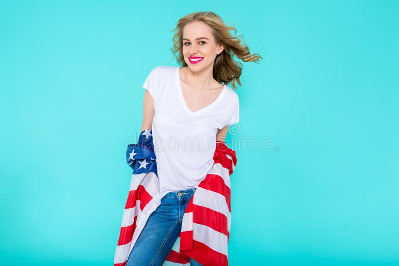 Αμερική ι αγάπη Ευτυχής νέα χαμογελώντας γυναίκα στα τζιν και την άσπρη αμερικανική σημαία εκμετάλλευσης μπλουζών και την εξέταση στοκ φωτογραφία με δικαίωμα ελεύθερης χρήσης