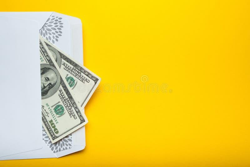 Αμερικανικά δολάρια σε έναν φάκελο που απομονώνεται σε ένα κίτρινο υπόβαθρο r στοκ φωτογραφίες