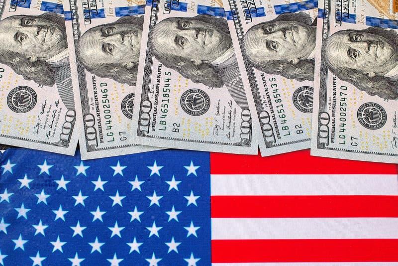Αμερικανικά δολάρια πέρα από σημαία των Ηνωμένων Πολιτειών στοκ εικόνα