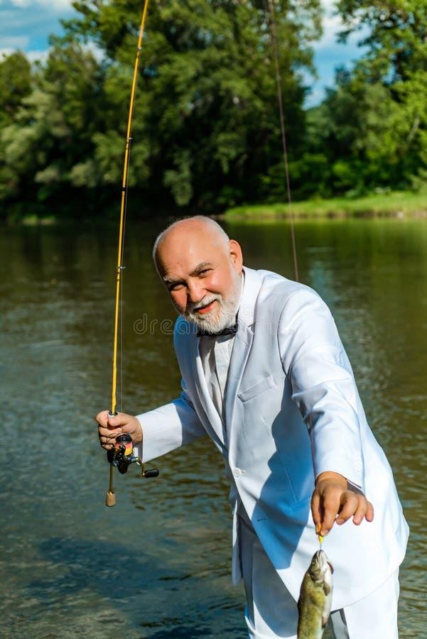 Αμερικανική αλιεία ψαράδων Ακόμα αλιεία πεστροφών νερού Όμορφος ώριμος ψαράς στο άσπρο κοστούμι που αλιεύει σε έναν ποταμό με το  στοκ εικόνα με δικαίωμα ελεύθερης χρήσης