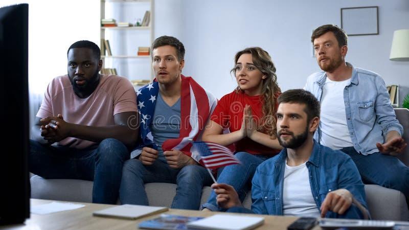 Αμερικανική αντιστοιχία προσοχής φίλων στη TV στο σπίτι, που υποστηρίζει την αγαπημένη ομάδα ποδοσφαίρου στοκ φωτογραφία