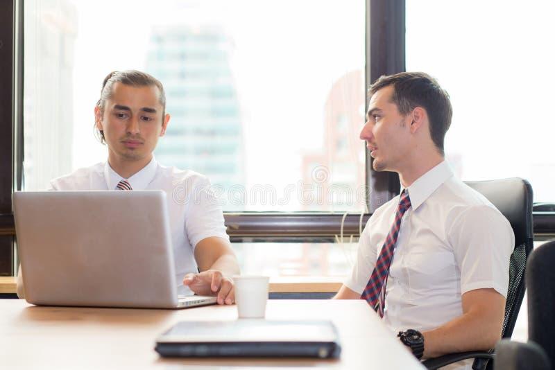 Αμερικανική επιχείρηση δύο ανθρώπων νέα καυκάσια σύγχρονη συνεδρίαση ατόμων σε μια αίθουσα συνεδριάσεων στοκ εικόνα