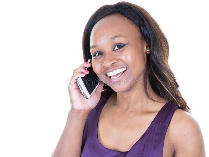 Αμερικανική ομιλία γυναικών afro χαμόγελου νέα στο τηλέφωνο κυττάρων στοκ φωτογραφία με δικαίωμα ελεύθερης χρήσης
