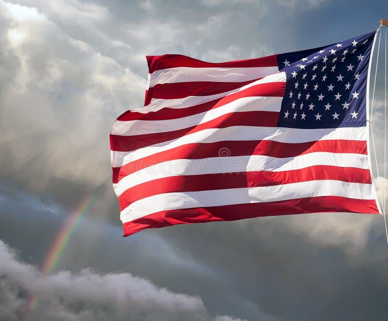 Αμερικανική σημαία ενάντια σε έναν νεφελώδη ουρανό με ένα ουράνιο τόξο στοκ εικόνες