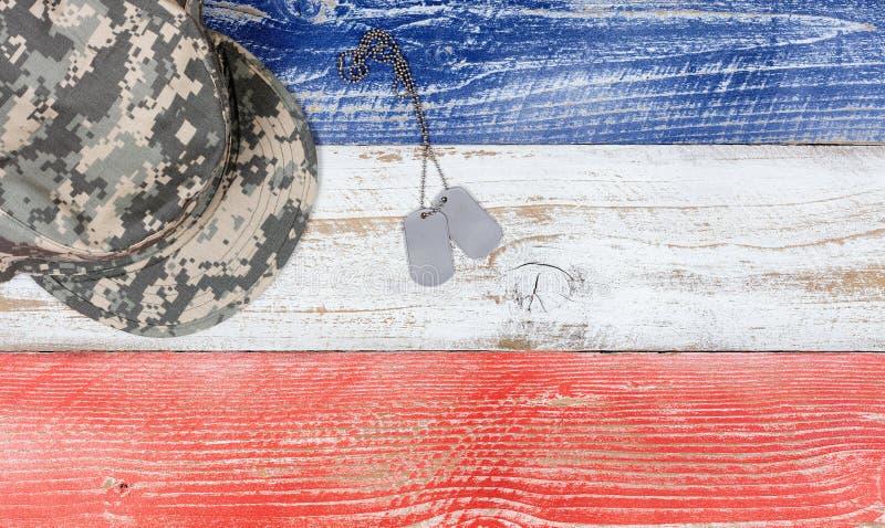 ΑΜΕΡΙΚΑΝΙΚΑ εθνικά χρώματα με τις στρατιωτικές ετικέττες ΚΑΠ και ταυτότητας στο ξύλινο σχέδιο στοκ φωτογραφία