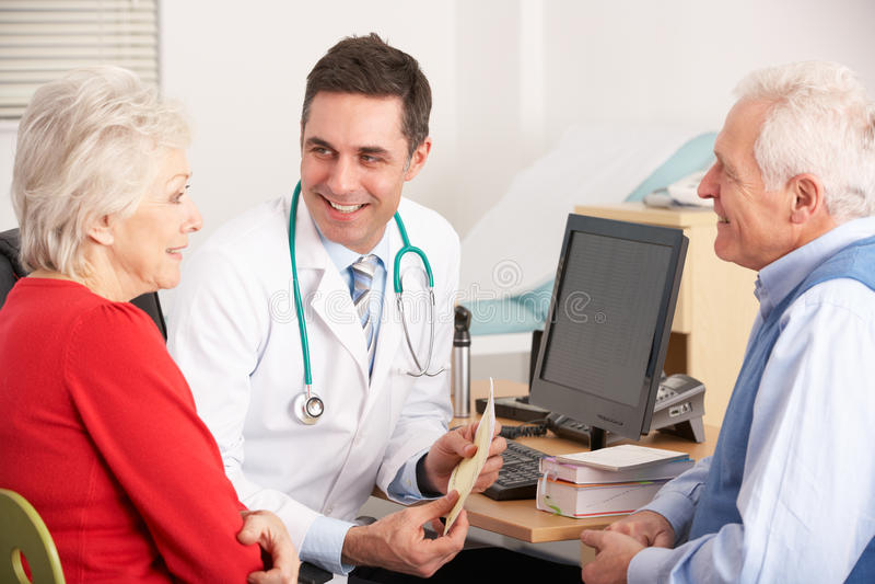 Αμερικανικός γιατρός που μιλά στο ανώτερο ζεύγος στοκ φωτογραφία
