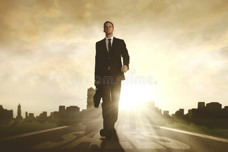 Αμερικανικός επιχειρηματίας που περπατά με τη λέξη πωλήσεων στοκ φωτογραφίες