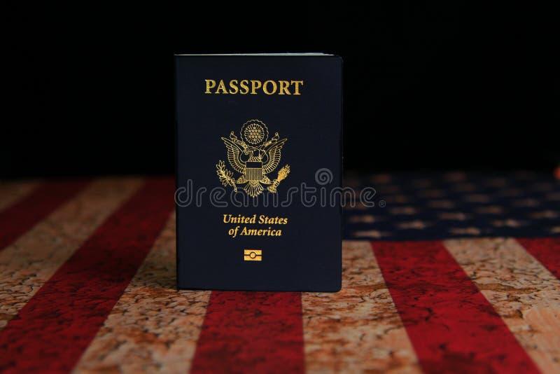 Αμερικανικό διαβατήριο που στέκεται στην αγροτική αμερικανική σημαία με το μαύρο υπόβαθρο στοκ φωτογραφίες