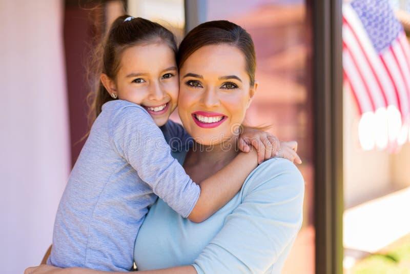 Αμερικανικό κορίτσι που αγκαλιάζει τη μητέρα στοκ φωτογραφία