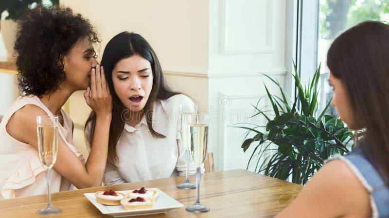 Αμερικανικό μυστικό αφήγησης κοριτσιών Afro στο αυτί στο φίλο της στοκ φωτογραφία με δικαίωμα ελεύθερης χρήσης