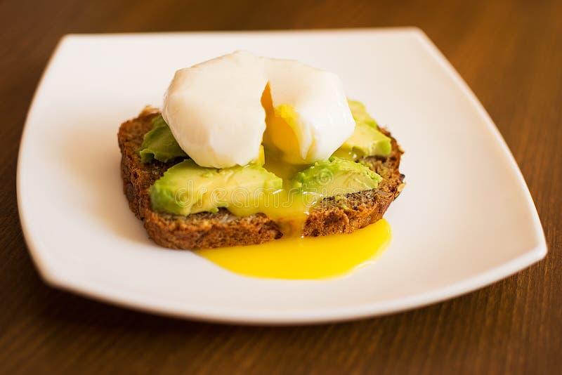 Αμερικανικό σάντουιτς αβοκάντο προγευμάτων και λαθραία αυγά στο ψωμί σίκαλης στοκ φωτογραφίες με δικαίωμα ελεύθερης χρήσης