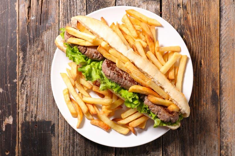 Αμερικανικό σάντουιτς με το βόειο κρέας και τις τηγανιτές πατάτες στοκ εικόνες