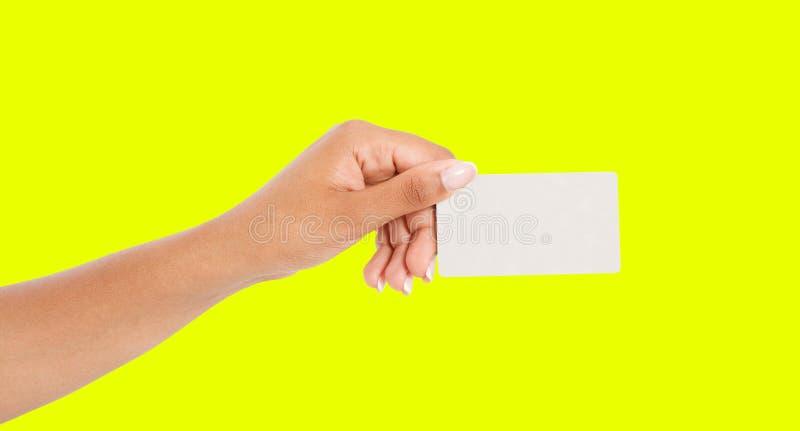 Αμερικανικό χέρι Afro που παρουσιάζει κάρτα εγγράφου που απομονώνεται στο κίτρινο υπόβαθρο, λαβή βραχιόνων businesscard στοκ εικόνα