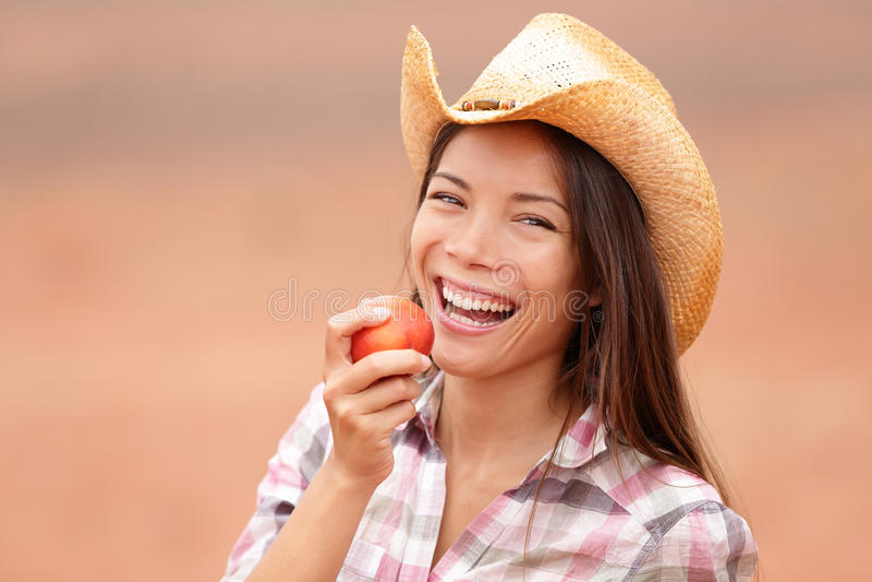 Αμερικανικό cowgirl που τρώει το χαμόγελο ροδάκινων ευτυχές στοκ εικόνα