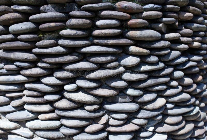 Αμμοχάλικο χαλικιών ποταμών γύρω από τον τοίχο πετρών που διαμορφώνεται για το υπόβαθρο Γκρίζο υπόβαθρο χαλικιών για το σπίτι και στοκ εικόνες