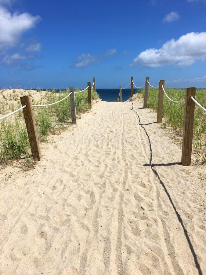 Αμμώδης διάβαση πεζών εισόδων παραλιών - ηλιόλουστη ημέρα με τον ωκεανό, χρώμα σύννεφων στοκ εικόνες