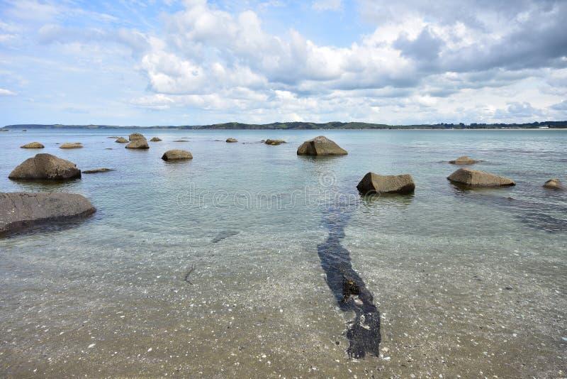 Αμμώδη ρηχά με ογκόλιθους στο νερό στοκ εικόνα
