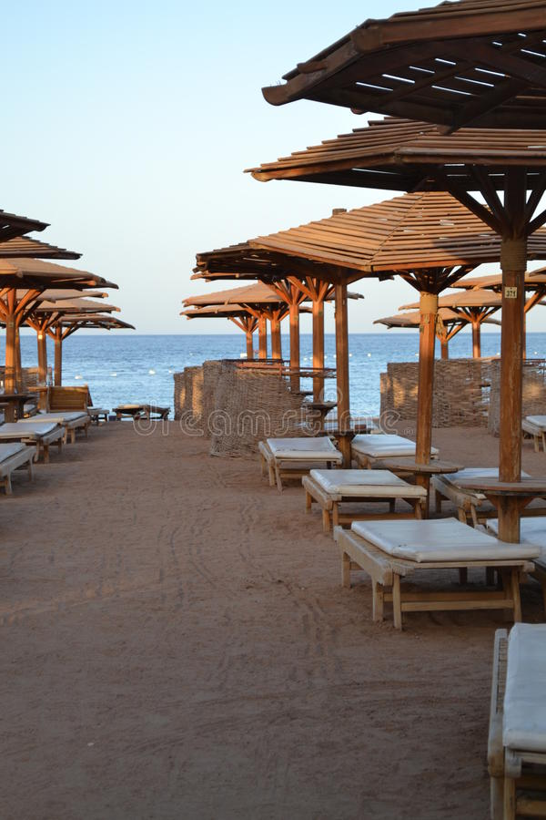 Αμμώδης παραλία κοντά στη θάλασσα με την ξύλινη ομπρέλα στοκ φωτογραφίες με δικαίωμα ελεύθερης χρήσης