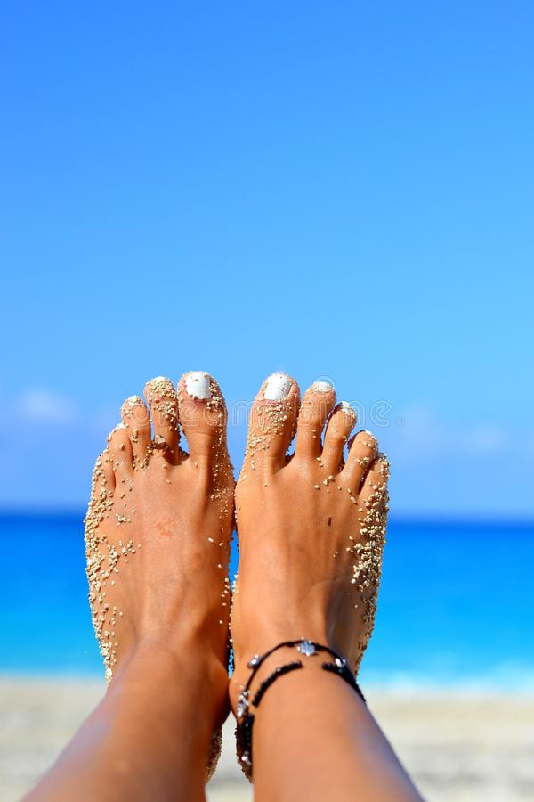 Αμμώδης πληρώνει με τα βραχιόλια στην παραλία, μπλε υπόβαθρο στοκ εικόνα