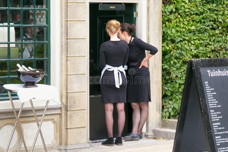 ΑΜΣΤΕΡΝΤΑΜ, ΚΑΤΩ ΧΏΡΕΣ - 25 ΙΟΥΝΊΟΥ 2017: Δύο άγνωστες σερβιτόρες στο μαύρο ομοιόμορφο φόρεμα κοντά στο Rijksmuseum στοκ φωτογραφίες