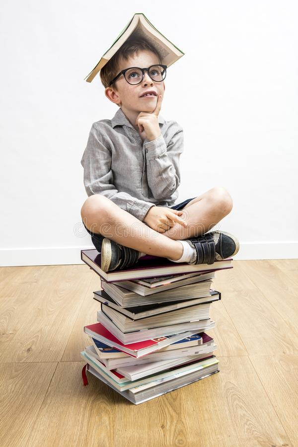 Αμφίβολος μαθητής με έξυπνα eyeglasses με το βιβλίο στο κεφάλι του στοκ εικόνα με δικαίωμα ελεύθερης χρήσης