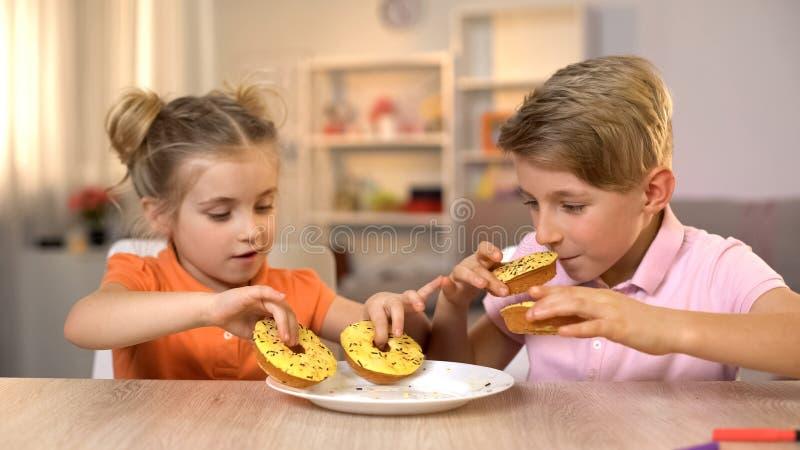 Αμφιθαλείς που παίρνουν και που μυρίζουν τα κίτρινα donuts, ανθυγειινό αλλά νόστιμο πρόχειρο φαγητό, τρόφιμα στοκ φωτογραφία