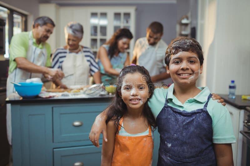 Αμφιθαλείς που χαμογελούν στη κάμερα ενώ οικογενειακά μέλη που προετοιμάζουν το επιδόρπιο στο υπόβαθρο στοκ φωτογραφία με δικαίωμα ελεύθερης χρήσης