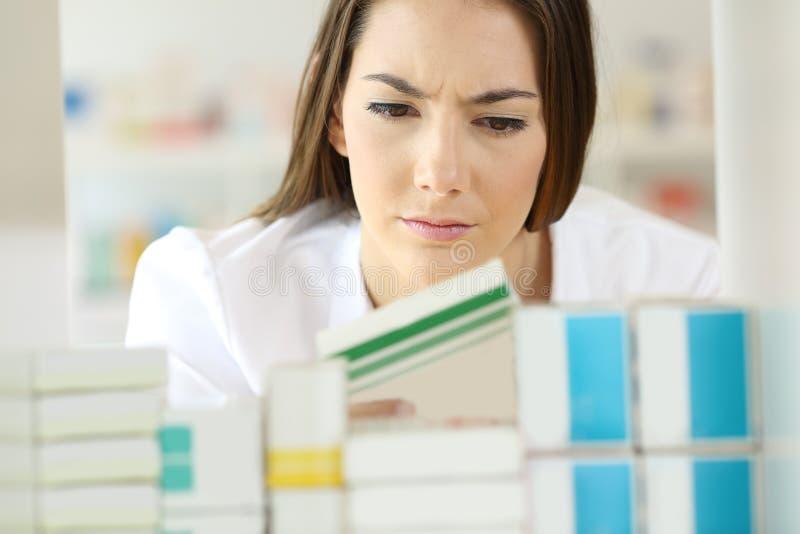 Αμφισβητήσιμος φαρμακοποιός που ελέγχει μια ιατρική στοκ φωτογραφία με δικαίωμα ελεύθερης χρήσης