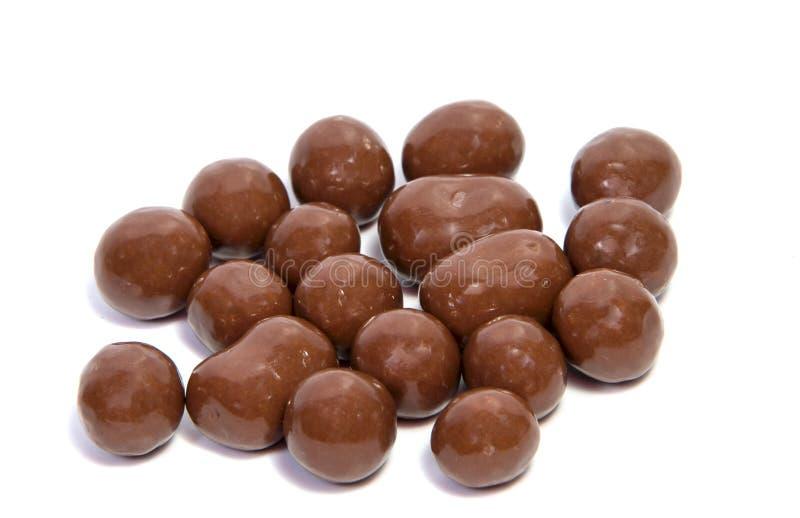 αμύγδαλα στο λούστρο σοκολάτας σε ένα άσπρο υπόβαθρο στοκ εικόνα