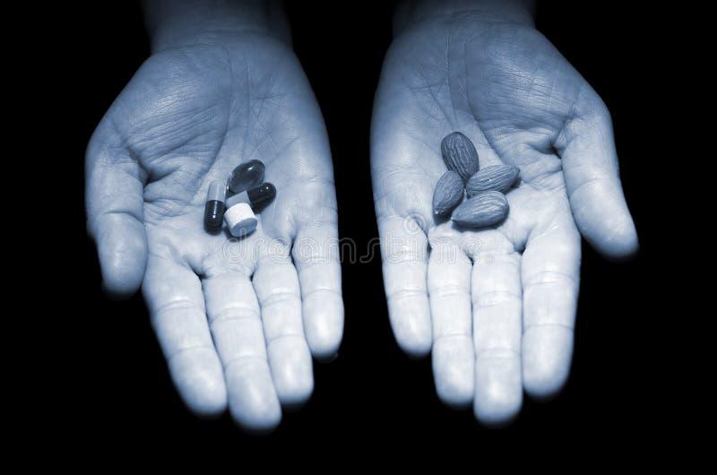 Αμύγδαλα εναντίον των χαπιών Ανθρώπινα χέρια ` s που κρατούν τα αμύγδαλα και τις ταμπλέτες στοκ φωτογραφία με δικαίωμα ελεύθερης χρήσης