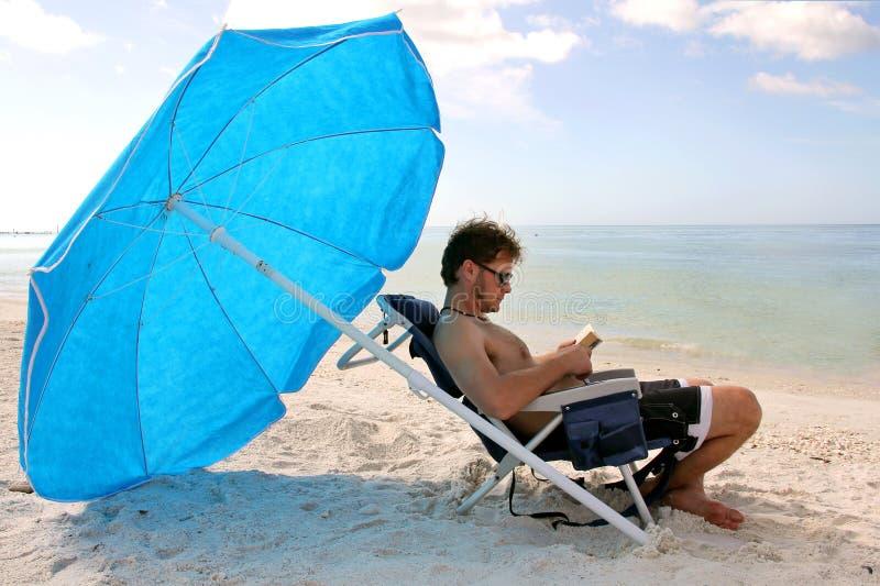 Ανάγνωση ατόμων από τον ωκεανό κάτω από την ομπρέλα παραλιών στοκ φωτογραφία με δικαίωμα ελεύθερης χρήσης
