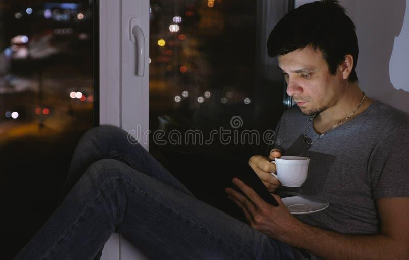 Ανάγνωση ατόμων κάτι στην ταμπλέτα και το τσάι κατανάλωσης Καθίστε στο windowsill στο σκοτάδι τη νύχτα στοκ εικόνα