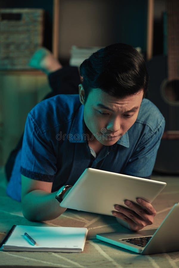 Ανάγνωση ατόμων κάτι στον υπολογιστή ταμπλετών στοκ φωτογραφία