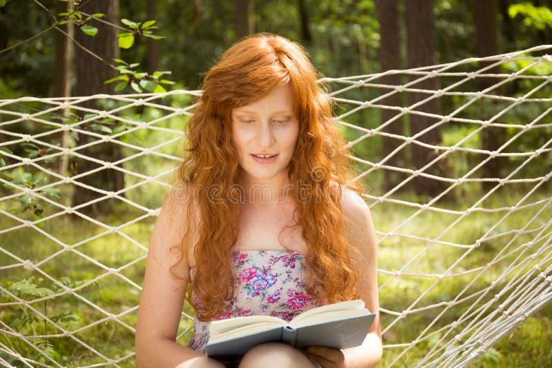 Ανάγνωση γυναικών σε μια αιώρα στον κήπο στοκ φωτογραφία με δικαίωμα ελεύθερης χρήσης