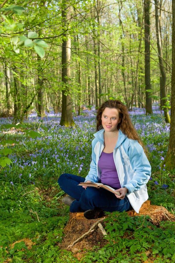 Ανάγνωση γυναικών στο δάσος wildflower στοκ εικόνες