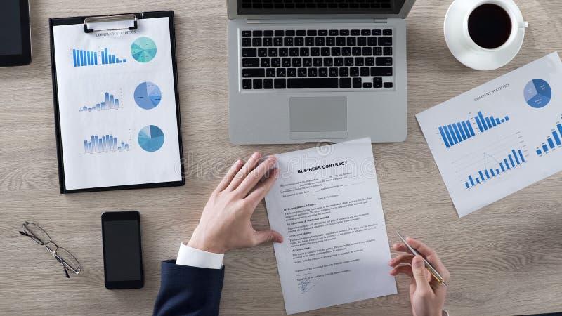 Ανάγνωση επιχειρηματιών και υπογραφή της επιχειρησιακής σύμβασης, εργασία γραφείων, τοπ άποψη στοκ φωτογραφίες