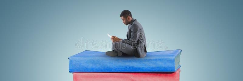 Ανάγνωση επιχειρησιακών ατόμων σε έναν σωρό από τα βιβλία και το γκρίζο υπόβαθρο στοκ εικόνα