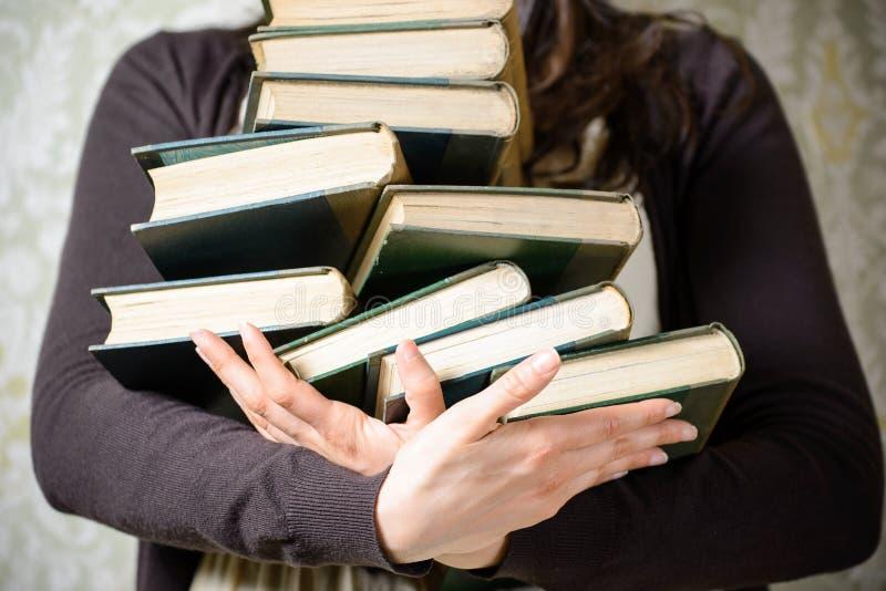Σπουδαστής που κρατά τα παλαιά βιβλία στοκ φωτογραφία