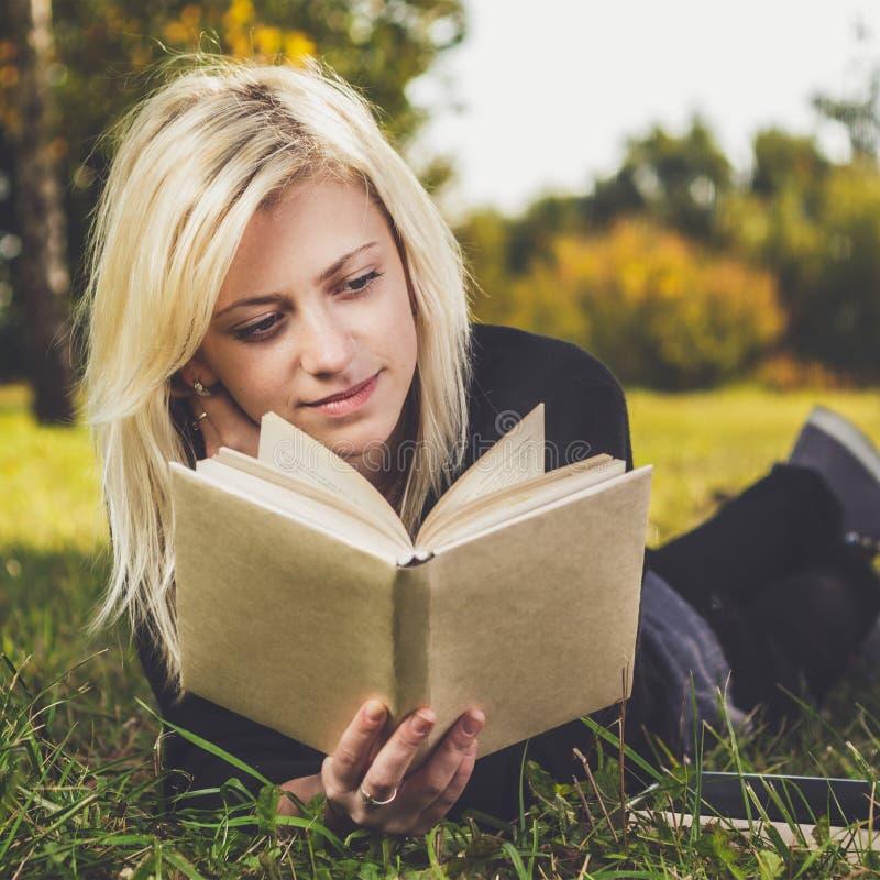 Ανάγνωση κοριτσιών στο πάρκο στη χλόη στοκ εικόνα