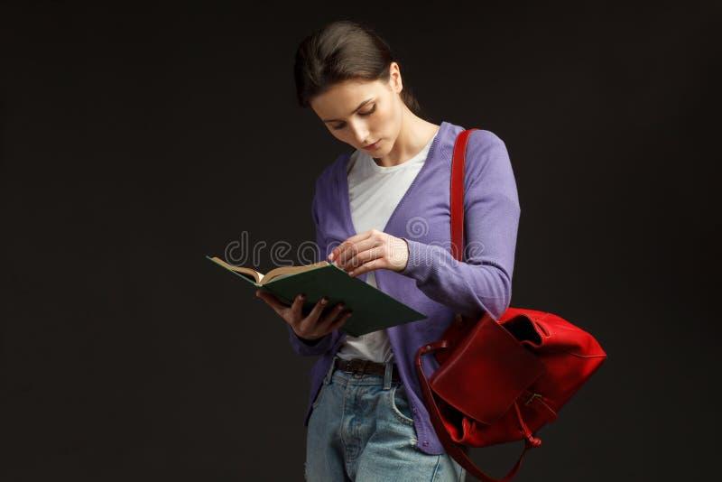 Ανάγνωση της γυναίκας σπουδαστή με τα βιβλία και το σακίδιο πλάτης στοκ φωτογραφίες