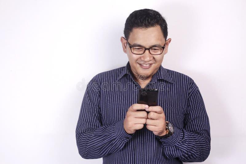 Ανάγνωση Texting νεαρών άνδρων που κουβεντιάζει στο τηλέφωνό του, χαμόγελο ευτυχές στοκ φωτογραφίες με δικαίωμα ελεύθερης χρήσης