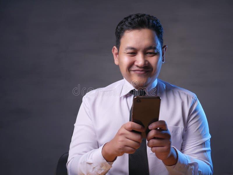 Ανάγνωση Texting νεαρών άνδρων που κουβεντιάζει στο τηλέφωνό του, χαμόγελο ευτυχές στοκ εικόνες με δικαίωμα ελεύθερης χρήσης