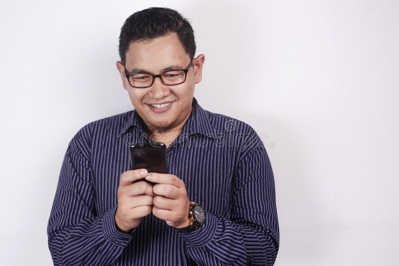 Ανάγνωση Texting νεαρών άνδρων που κουβεντιάζει στο τηλέφωνό του, χαμόγελο ευτυχές στοκ εικόνα