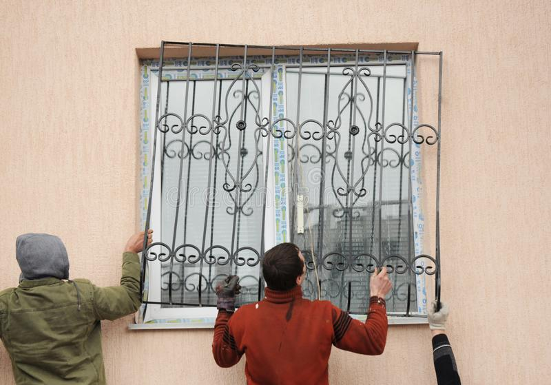 Ανάδοχοι οικοδόμων που εγκαθιστούν τους φραγμούς ασφάλειας σιδήρου παραθύρων για την προστασία στοκ φωτογραφία