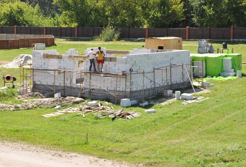 Ανάδοχοι που χτίζουν το νέο σύγχρονο σπίτι από τους αερισμένους τσιμεντένιους ογκόλιθους στοκ εικόνες