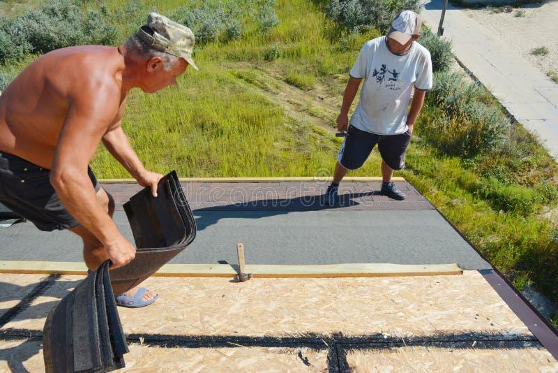 Ανάδοχοι Roofer που βάζουν και που εγκαθιστούν τα βότσαλα ασφάλτου Κατασκευή υλικού κατασκευής σκεπής με τη στέγη στοκ εικόνες με δικαίωμα ελεύθερης χρήσης