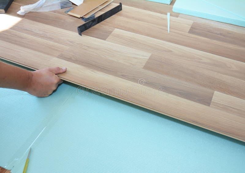 Ανάδοχος που εγκαθιστά το ξύλινο φυλλόμορφο δάπεδο με τη μόνωση και τα sound-proofing φύλλα δαπεδώνοντας φυλλόμορφο βάζοντας άτομ στοκ εικόνες