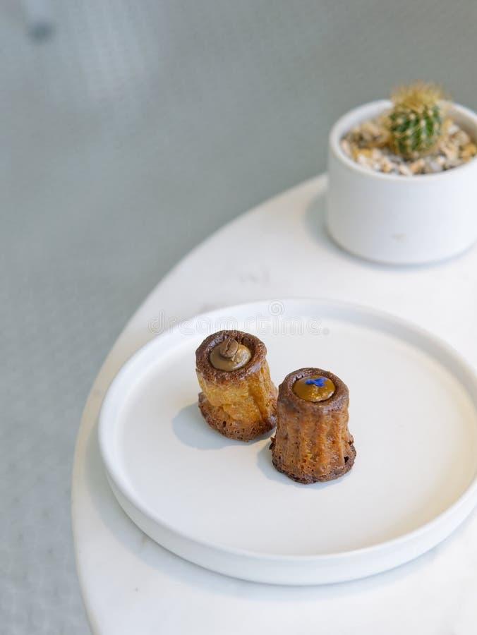 Ανάμεικτα canneles στο άσπρο στρογγυλό πιάτο στον άσπρο μαρμάρινο πίνακα με τις εγκαταστάσεις κάκτων θαμπάδων στοκ φωτογραφία